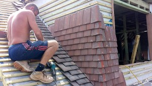 Here the roofer is pinching in the tiles on the dormer, while topping up his tan!