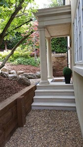 Through the portico you can see built in the retaining wall at the end of the path, is a peaceful water feature.